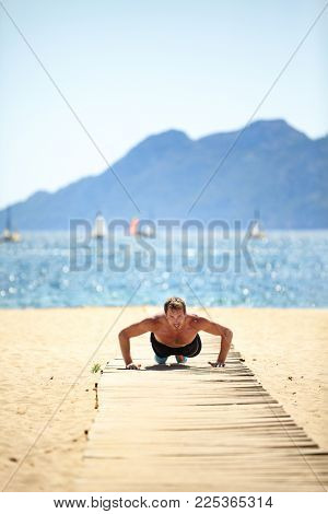 Sport beach fitness man doing push-ups. Handsome athlete training push up topless outside in summer sun. Fit male fitness model doing exercise outdoors. Healthy lifestyle concept. Active lifestyle.