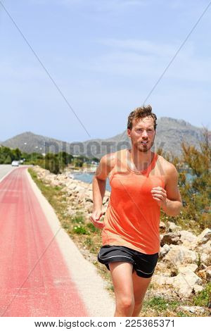 Exercise outdoor fitness man jogging on street training cardio outside in summer heat sweating. Sport athlete running in tank top sports clothes.