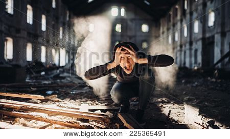 Sad depressed person in abandoned destroyed building crying.Emotional portrait.Mentally ill woman with bipolar disorder and psychosis.Schizophrenia.Madness, crazy person.
