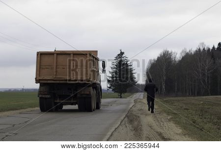 A sportsman is running away  on a higway with cargo truck passing by in countryside landscape.