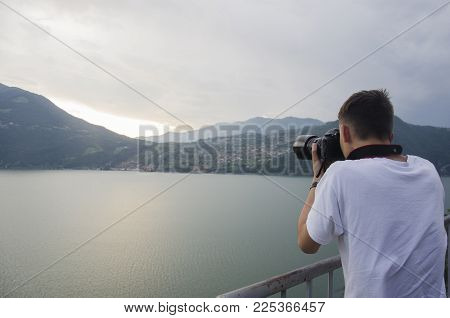 Photographer taking a picture at the sunset over the Italian Alps, Italy. Beautiful sunset ovet the high mountines. Young photographer taking his best pictures
