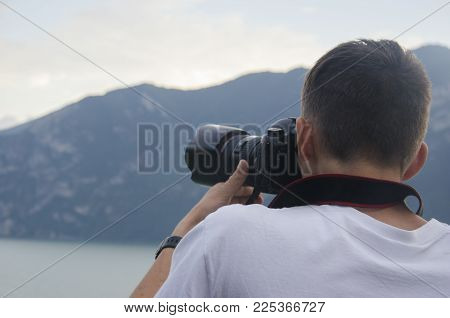 Close-up photographer taking a picture at the sunset over the Italian Alps, Italy. Beautiful sunset ovet the high mountines. Young photographer taking his best pictures