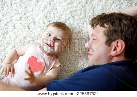 Happy proud young father having fun with baby daughter, family portrait together. Dad with baby girl, love. New born child looking on dad. Bonding, family, new life