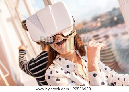 Advanced VR. Cheerful optimistic energetic woman wondering when wearing VR glasses and opening mouth