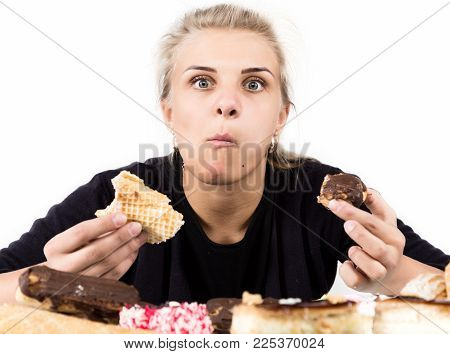 glutton woman eating cupcakes with frenzy after long diet. harmful but delicious food