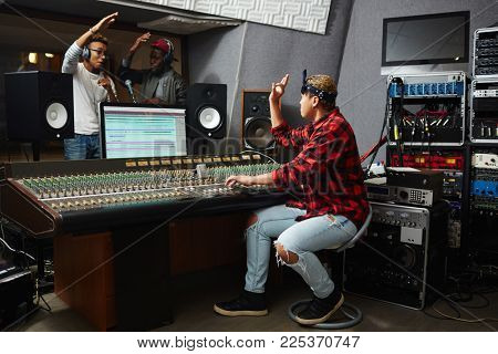 Sound operator showing okay gesture to young musicians while recording their songs in audio studio