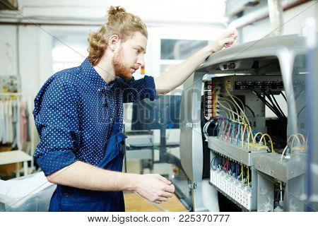 Young service staff trying to find out cause of malfunction of graphic printing machine