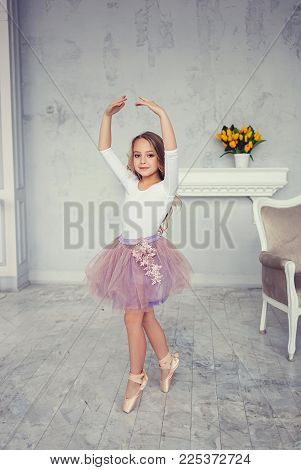 A cute little girl is dancing like a ballerina in a room. Dreams of childhood