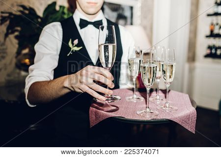 waiter brings glasses of champagne and  tray