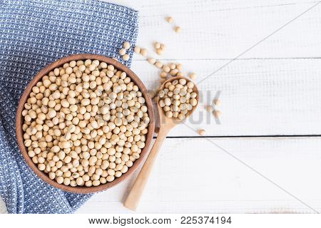 White wood floor with wooden cup with soybean,top view and copy space,soybeans in wooden bowl with wooden spoon on table wooden