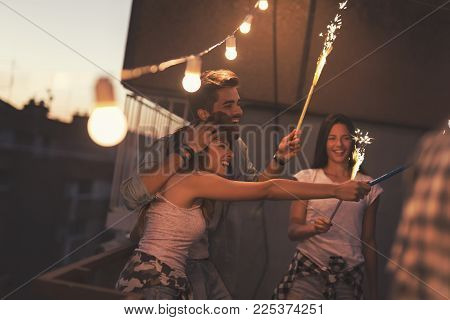 Group of young friends having fun at a rooftop party, singing, dancing and waving with sparklers