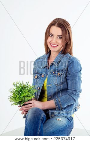 Studio portrait of beautiful young smiling woman wearing blue jeans and denim jacket, sitting over white background, holding houseplant. Casual style.