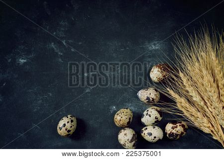 A bunch of wheat ears next to quail eggs on a black table, top view.