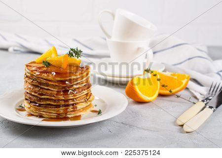 Table of breakfast . Pancakes with orange and sprinkled maple syrup, orange juice and coffee
