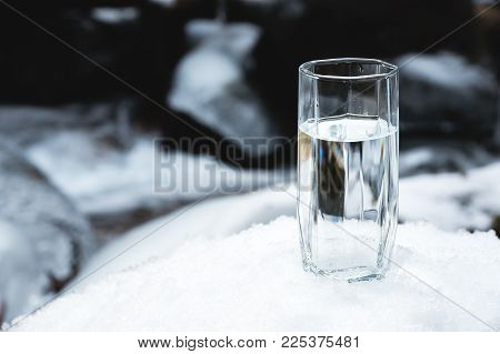 A transparent glass glass with drinking mountain water stands in the snow against a background of a clean frost mountain river in winter. The concept of drinking mountain drinking mineral water and the production of mineral environmentally friendly