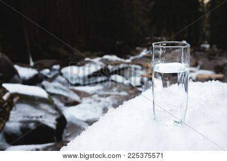 A transparent glass glass with drinking mountain water stands in the snow against a background of a clean mountain river and a forest in winter. The concept of drinking mountain drinking mineral water and the production of mineral environmentally friendly