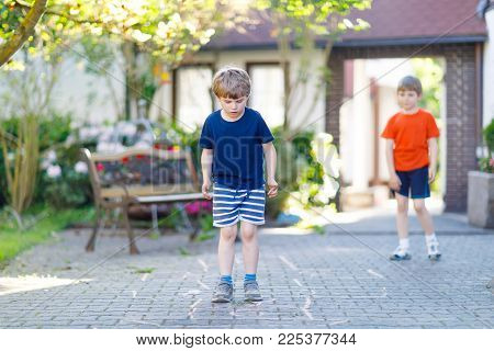 Two little school and preschool kids boys playing hopscotch on playground outdoors together. children having fun with outdoor activities in summer on sunny day. Best friends