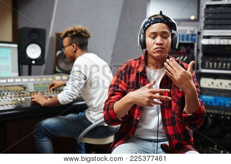 Young African-america woman performing songs while sound operator recording her voice