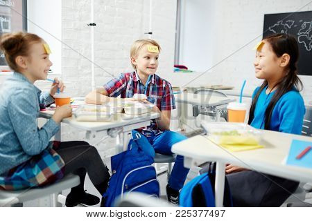 Cute classmates sitting in classroom and playing name game at lunch break