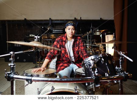 Young contemporary drummer sitting in studio or garage in front of drum set