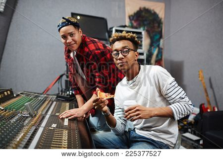 Man with pizza and drink and his colleague spending working day in sound recording studio