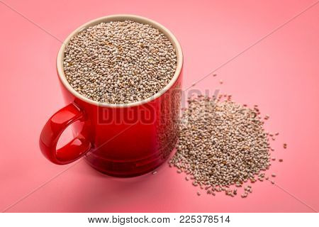 a small coffee cup of organic white chia seeds rich in omega-3 fatty acids against pink background