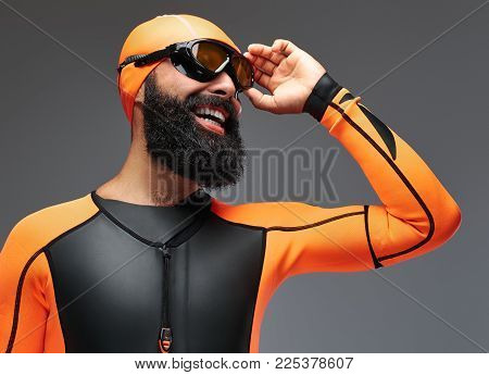 Close-up portrait of a smiling bearded male in orange neoprene diving suit and dive mask isolated on grey background.