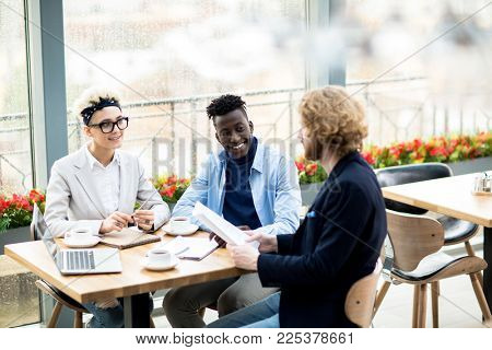 Young intercultural colleagues listening to report of their co-worker while sitting by table in cafe