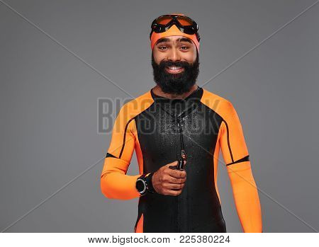 Portrait of a smiling bearded male in orange neoprene diving suit and dive mask isolated on grey background.