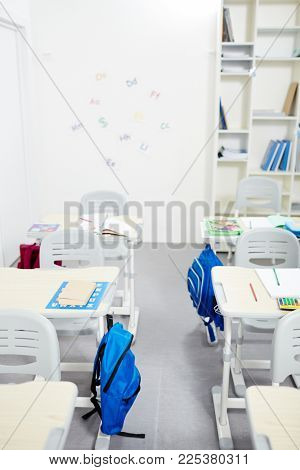 Aisle between two rows of desks with school supplies in empty classroom