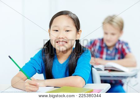 Asian schoolgirl and her classmate on background drawing at lesson by individual seats