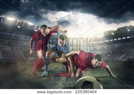 The football player in motion on the field of stadium with lights. The professional football, soccer player and human emotions concept. The attack, defense, fight concepts