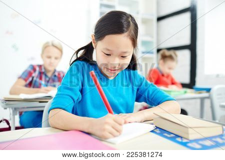 Asian elementary school learner with red crayon drawing on sheet of paper at lesson with classmates on background