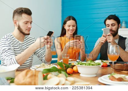 Three young people with gadgets searching in web while sitting by festive table after dinner