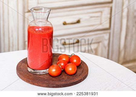 Close up glass bottle of tomato juice with fresh tomatoes on wooden board used for cooking borscht. Selective focus