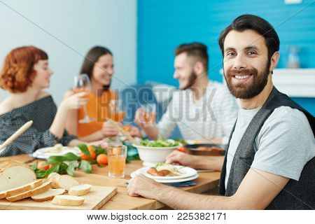 Happy bearded man with toothy smile sitting by festive table with his friends