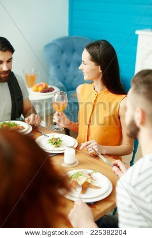 Young woman with glass of juice looking at one of her friends while talking or listening to him during dinner