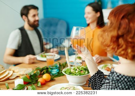 One of girls holding glass of juice in hand while sitting by festive table among her friends