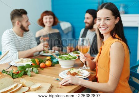 Pretty young housewife with wineglass of juice sitting by served table with her guests