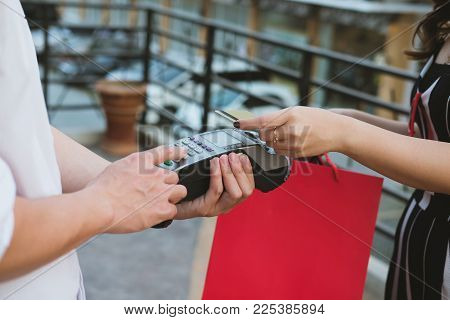 Man Make Payment With Credit Card Swipe Through Terminal. Customer Paying & Entering Code With Swipi