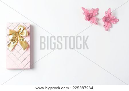 gift box of pink color with a bow of gold, two beautiful figures of birds. blank space for a text, flat lay