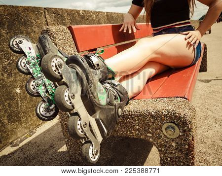 Woman Wearing Roller Skates Sitting On Bench With Raised Legs. Bizarre Angle