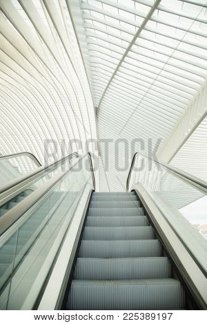 Escalator going up with a nice architecturall glass and cement roof top