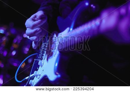 artist Guitarist hand play electricity guitar on concert stage with blue light, Practicing in playing . song entertainment and music instrument