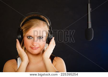 Music, Passion, Stage-fright Concept. Blonde Young Woman Singing To Microphone And Wearing Big Headp