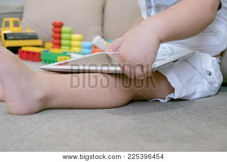 Toddler Boy Playing With Digital Tablet On Couch At Home