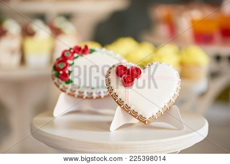Round And Heart Shaped Glazed Cookies, Decorated With Glaze Flowers And Pattern Are On The Wooden St