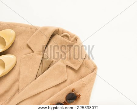 Spring autumn female outfit. Set of clothes, shoes and accessories on white background. Camel coat and cream shoes