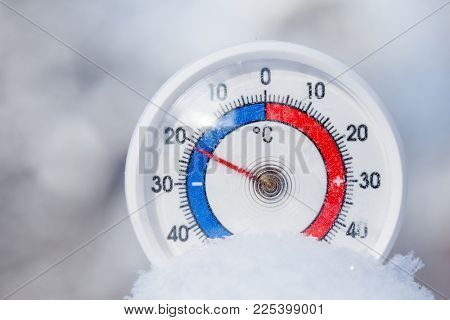 Thermometer with celsius scale placed in a fresh snow showing sub-zero temperature minus 21 degree - cold winter weather concept