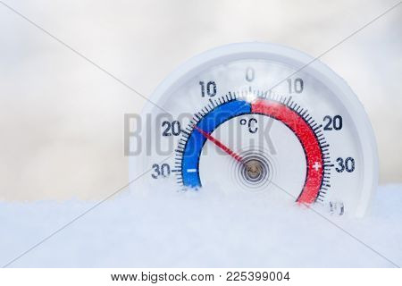 Thermometer with celsius scale placed in a fresh snow showing sub-zero temperature minus 17 degree - cold winter weather concept
